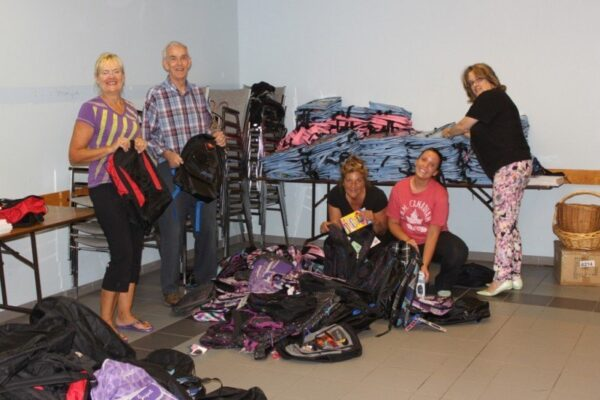 Pam Garniss, Angela Baglieri, Romy Scott, John Lowe and Janet Lowe get the backpacks ready