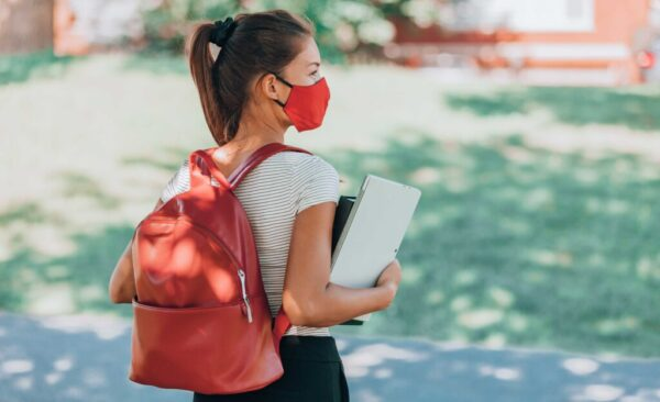 Young girl with backpack wearing a mask